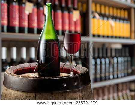 Wine bottle and glass of red wine on wooden cask. Wine shelves at the background.