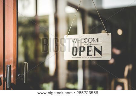 Open Sign Hanging Front Of Cafe With Colorful Bokeh Light Abstract Background. Business Service And