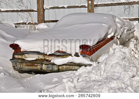 An Old Rusty Car Is Buried In A Snowdrift With Only Blinkers, Taillights And Bumper Exposed.