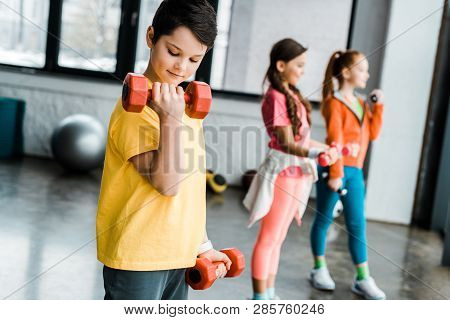 Preteen Kids Training With Dumbbells In Gym
