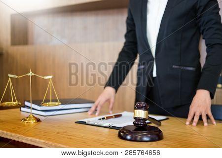 Lawyer Judge Reading Documents At Desk In Courtroom Working On Wooden Desk Background. Gavel  Golden