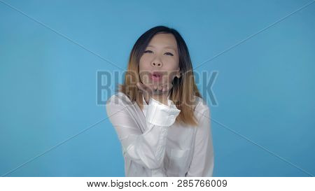 Young Asian Woman Posing Sends An Air Kiss To The Audience On Blue Background In Studio. Attractive