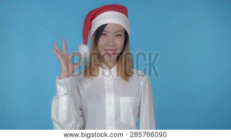 Young Asian Woman Posing Wearing Santa Claus Hat Showing Symbol Hand Gesture Ok On Blue Background I