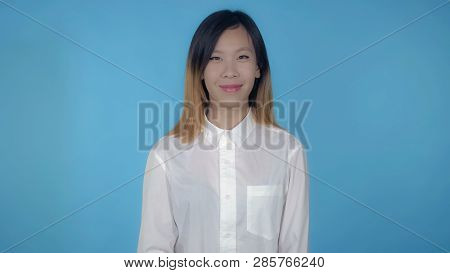Young Asian Woman Posing On Blue Background In Studio. Attractive Millennial Girl Wearing White Casu