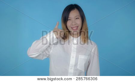Young Asian Woman Posing Showing Hand Gesture Like On Blue Background In Studio. Attractive Millenni