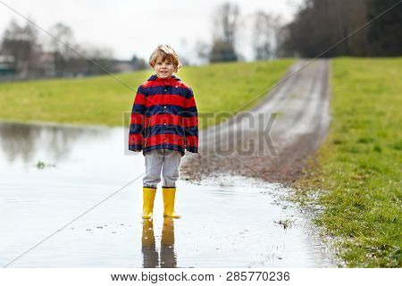 Little Kid Boy Wearing Yellow Rain Boots And Walking And Jumping Into Puddle On Warm Sunny Spring Da