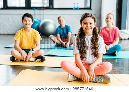 Excited Kids Stretching On Fitness Mats In Gym