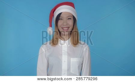Young Asian Woman Posing Wearing Santa Claus Hat On Blue Background In Studio. Attractive Millennial
