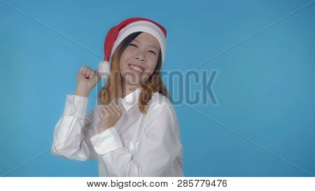 Young Asian Woman Posing Wearing Santa Claus Hat Dancing On Blue Background In Studio. Attractive Mi