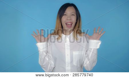 Young Asian Woman Posing Showing Happiness Joyful Mood On Blue Background In Studio. Attractive Mill