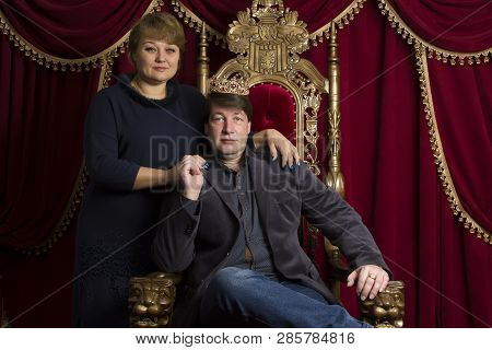 Husband And Wife In A Beautiful Chair. Husband Is King Wife Queen. Middle Aged Couple
