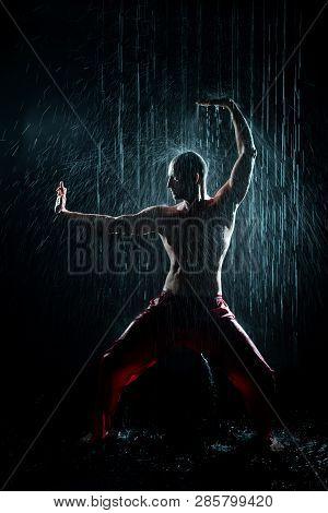 Shirtless Man Doing Qigong Under The Rain