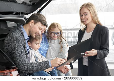 Beautiful Woman Working As Car Dealer, Holding Black Folder With Document. Man Signing Contract, Pur