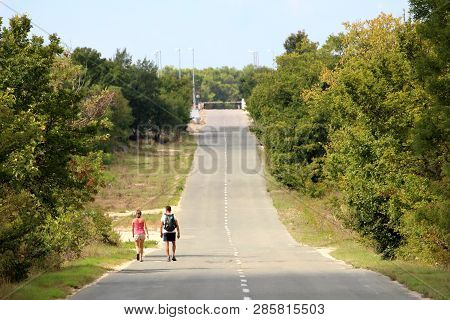 Two Backpacker Tourists Walking On Long Straight Paved Road Going Uphill Towards Closed Site With Ra