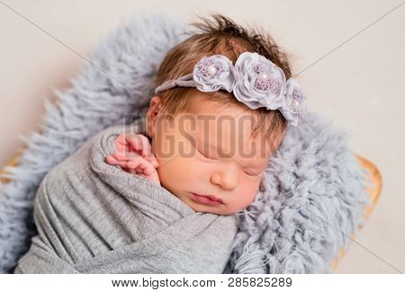 Cute little baby with knitted toy bunny lying on the gray pillow covered with gray coverlet