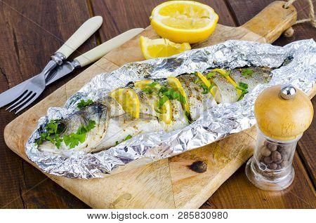 Fish Carcass Dicentrarchus Labrax With Lemon, Baked In Foil With Spices.