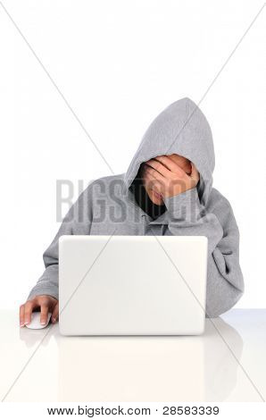 Frustrated Teen Girl with her head in her hand as she sits in front of her laptop computer. Teenager is wearing a hoodie sweatshirt over a white background.