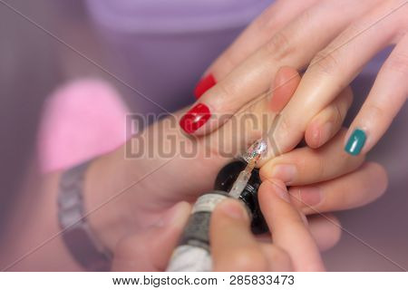 Woman receiving fingernail manicure service by professional  manicurist at nail salon. Beautician painting nails at nail and spa salon. Focused on white and glitter nail polish at nail salon. poster