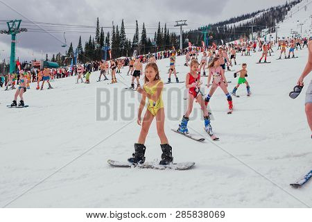 Sheregesh, Kemerovo Region, Russia - April 14, 2018 : Little Girl In Swimmingsuit Riding Snowboard O