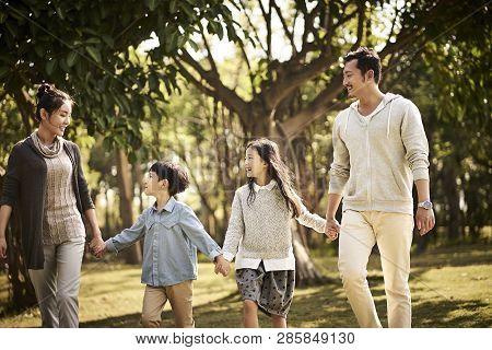 Asian Family With Two Children Walking Relaxing In Park Happy And Smiling.