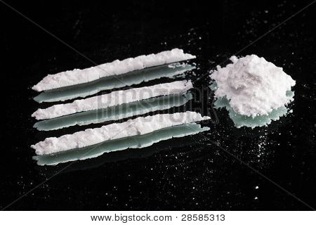 Cocaine drugs heap and lines still life on a dark mirror, close up view