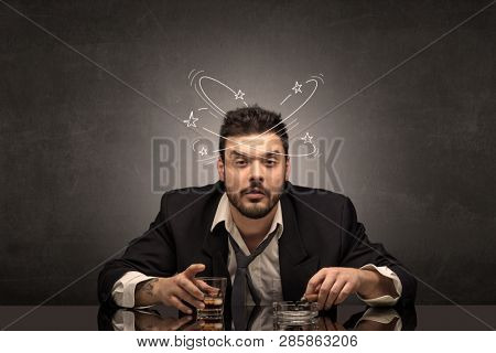 Young drunk man at his office with doodles around
