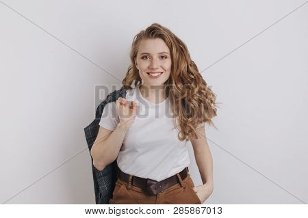 Nice Smiling Woman In A White T-shurt Holding Her Jacket Posing Isolated Over The White Background