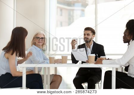 Five Diverse Workers Gathered Together In Boardroom