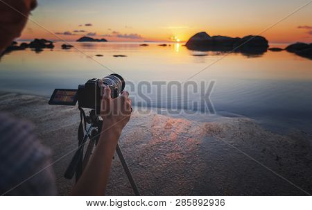 Photo Camera On Tripod On The Beach At Sea Sunset. Hobby Travel Photography Concept. Beautiful Sea L