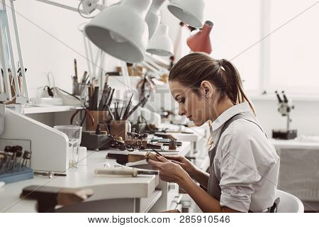 Working All Day. Side View Of Young Female Jeweler Sitting At Her Jewelry Workshop And Holding In Ha