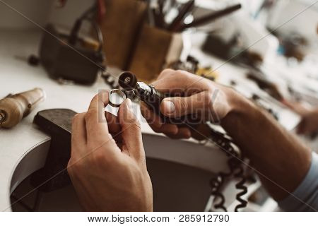 On The Way To Perfection. Close-up Of Male Jewelers Hands Polishing Silver Ring At His Jewelry Makin