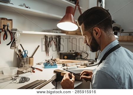 A Lot Of Work In The Workshop. Close Up Of A Young Male Jeweler Working And Shaping An Unfinished Ri