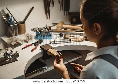 Focused On A Process. Back View Of A Female Jeweler Working And Shaping An Unfinished Ring With A To