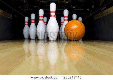 Orange Bowling Ball And Skittles Stand On A Wooden Bowling Alley