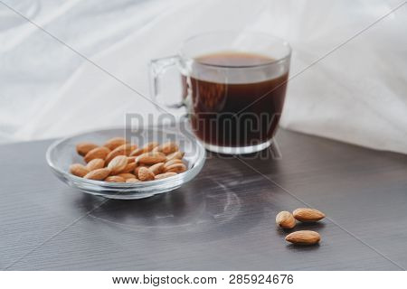 Concept Of Helathy Snack - Almonds With Coffee Placed On A Dark Laminate Wood Surface With White Cur
