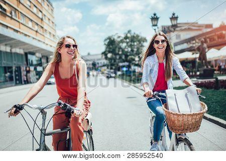 Two Beautiful Women Shopping On Bike In The City