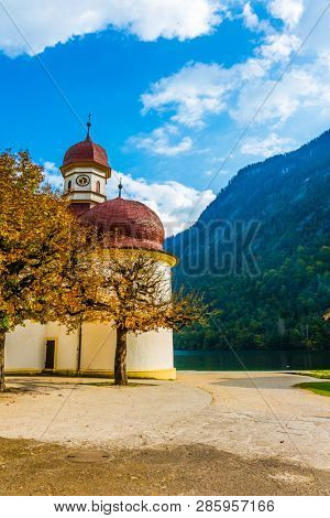 Charming church on the shore of a mountain lake Königssee. Mountain Lake is a fabulous beauty in Bavaria. The lake is surrounded by high mountains. The concept of active, ecological and photo tourism
