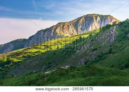 Beautiful Landscape Of Romania Mountains. Springtime Nature At Sunrise. Distant Cliff In Morning Lig