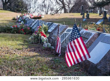 American flags and headstones at a cemetery- Memorial Day display poster