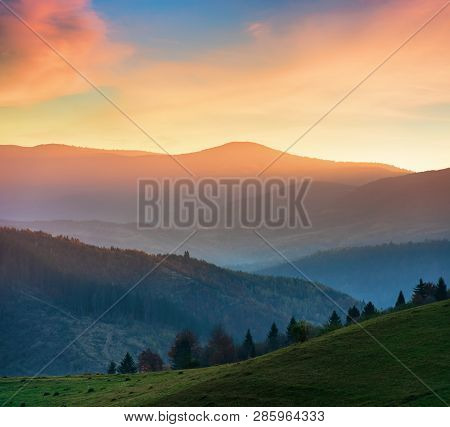 Beautiful Autumn Scenery In Mountains At Sunset. Red Clouds On The Sky, Blue Shade In The Mountains,