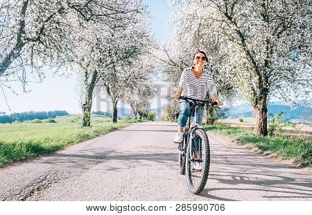 Happy Smiling Woman Rides A Bicycle On The Country Road Under Blossom Trees. Spring Is Comming Conce