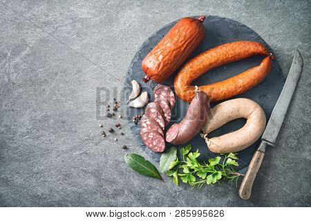 Assortment of german homemade sausage specialties: hard cured salami, liver sausage (Leberwurst), blood sausage (Blutwurst) and salami on kitchen table
