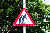 Beware of the elderly traffic sign on the light pole. Triangle traffic sign for the warnings. poster