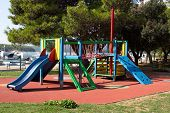 Multifunctional outdoor public playground equipment with blue plastic slide next to climbing net and wall connected with safety net tunnel on local playground surrounded with grass and trees with sea in background on warm sunny day poster