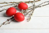 Red dyed Easter eggs and pussy willow on wooden table, space for text poster
