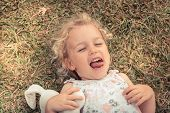 Happy cute mischievous smiling child girl fooling lying on grass concept happiness carefree childhood lifestyle poster