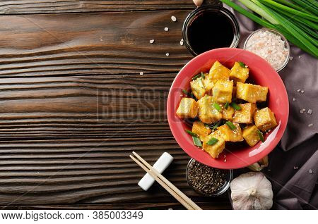Flat Lay View At Stir Fried Tofu Cubes With Chives In Clay Dish On Wooden Kitchen Table With Napkin