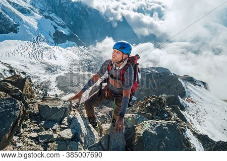 Climber In A Safety Harness, Helmet With Backpack Asceding A Rock Wall With Bionnassay Glacier On Ba