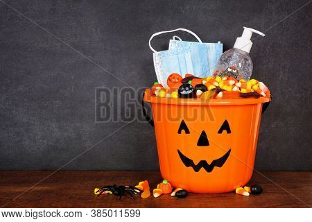 Halloween Jack O Lantern Pail With Candy And Coronavirus Prevention Supplies On A Shelf Against A Da