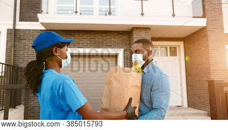 African American Female Courier In Medical Mask Delivering Bag With Food To Male Client At House And